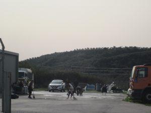 λαθρομετανάστες καθαρίζουν μπροστά από την αποθήκη που φιλοξενούνται.